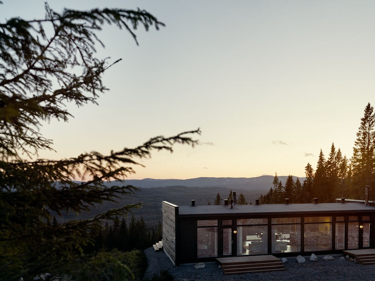 Kortsidene av hytten er i tømmer og langsidene er i fasadeglass.