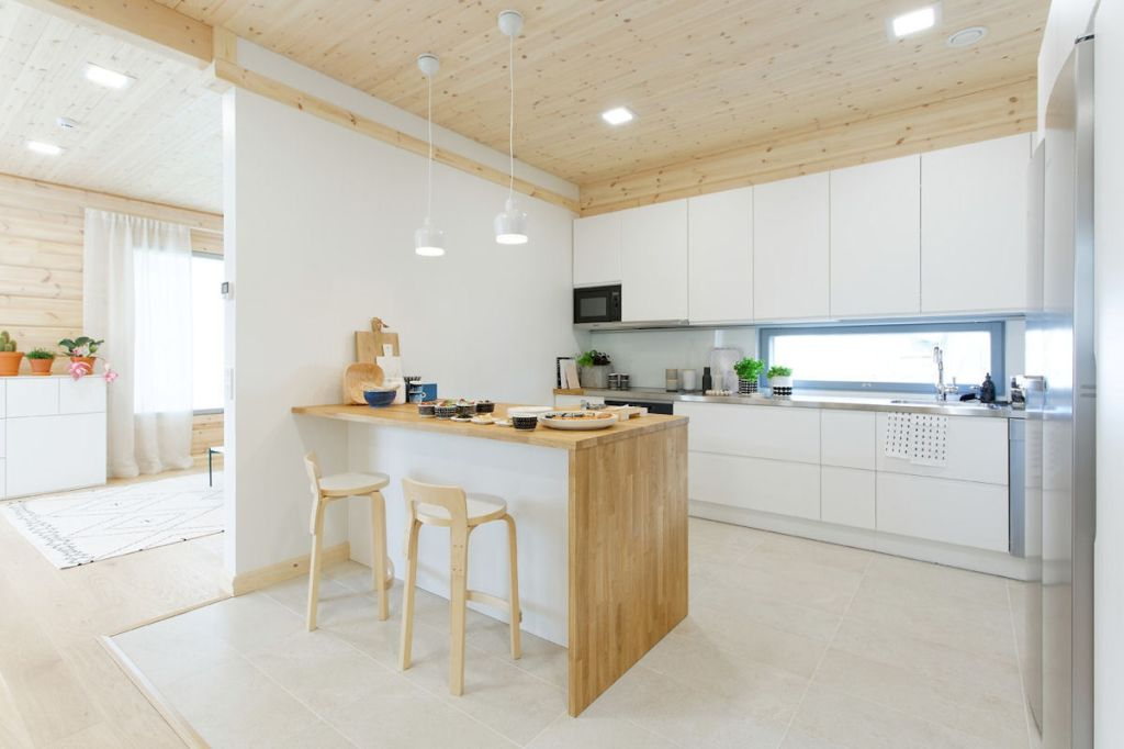 Valkoinen keittiö, kuten kodin kaikki kiintokalusteet, on Kontio Living-mallistoa. K65-jakkarat ja Golden Bell-valaisimet, Artek, Siirtolapuutarha-astiat, Marimekko. Teepannu ja japanilaiset astiat, Tokyokan. Viilu-pärekori ja puukranssi, Verso Design, tarjotin, Mayn.